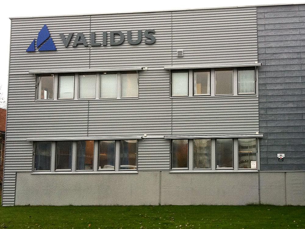 Logosymbol og tekst i sargbokstaver montert rett på fasaden.